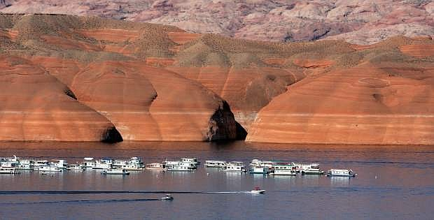 FILE - Houseboats are moored on Lake Powell in Bullfrog, Utah, in this July 12, 2006 file photo. The lake's former, higher levels are marked by the bathtub-like rings on the embankment, rear.  After back-to-back driest years in a century on the Colorado River, federal water managers are announcing a historic step to slow the flow of water from a massive reservoir upstream of the Grand Canyon to the huge Lake Mead reservoir behind Hoover Dam near Las Vegas. The U.S. Bureau of Reclamation is announcing Friday, Aug. 16, 2013, that the move to keep more water in Lake Powell will lower the water level of Lake Mead by about 20 feet in 2014. (AP Photo/Douglas C. Pizac, File)