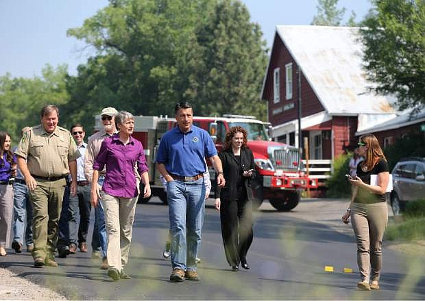 U.S. Secretary of the Interior Sally Jewell, left center, and Nevada Gov. Brian Sandoval, center, receive a briefing from fire officials on the Washington fire in Markleeville, Ca. on Wednesday, June 24, 2015. The lightning-caused fire has grown to nearly 17,000 acres since Friday. (AP Photo/Cathleen Allison)