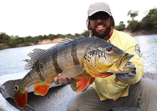 Fallon resident Denis Isbister shows off an 18-pound peacock bass during a fishing trip in Colombia in March.