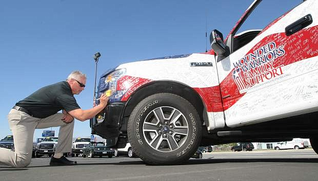 Capital Ford General Manager Tim Milligan signs one of two Ford vehicles traveling in the sixth annual Wounded Warriors High Five Tour on Tuesday. The event visits American cities to thank military families for their sacrifices.