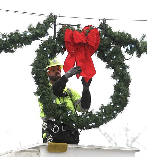 Gary Wood re-hangs a wreath on a guide wire after last week's wind storm forced the removal of some holiday decorations on Carson Street.