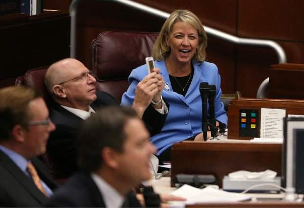 Nevada Senators Joe Hardy, R-Boulder City, and Barbara Cegavske, R-Las Vegas, react to their final vote during the second day of a special session at the Nevada Legislature, in Carson City, Nev., on Thursday, Sept. 11, 2014. Lawmakers are considering a complex deal to bring Tesla Motors to Nevada. (AP Photo/Cathleen Allison)