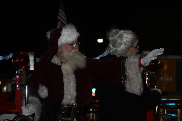 Santa and Mrs. Claus wave to visitors from the 1927 Seagrave fire engine from Warren Engine Co. during the annual Silver & Snowflakes Festival of Lights on Friday.