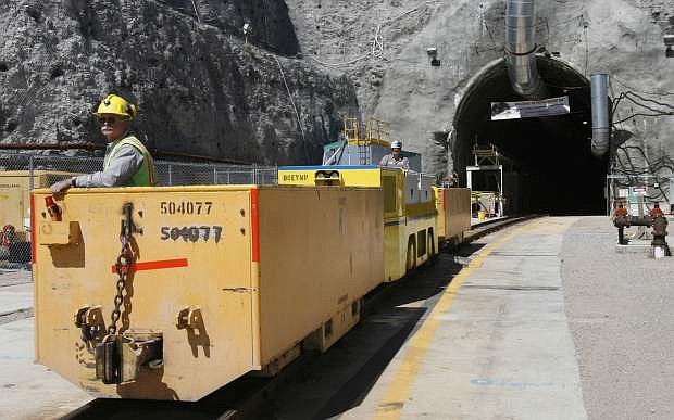 FILE - In this April 13, 2006 file photo, Pete Vavricka conducts an underground train from the entrance of Yucca Mountain in Nevada. Federal nuclear regulators say the U.S. Energy Department will need to acquire water rights and a land buffer before it can entomb the nation's radioactive waste beneath a long-studied volcanic ridge in the Nevada desert. The Nuclear Regulatory Commission issued a report Thursday, Dec. 18, 2014, saying most administrative and program elements of the Yucca Mountain repository meet commission requirements.  (AP Photo/Isaac Brekken, File)