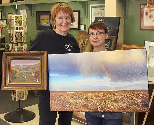 Patricia Sammons, left, owner of the Rising Sun Gallery and Art Studio, and Erin Roach, a junior at Churchill County High School, hold a painting and canvas photogrpah, respectively. The artwork, along witgh other offerins, will be auctioned at Saturday's fundraiser.
