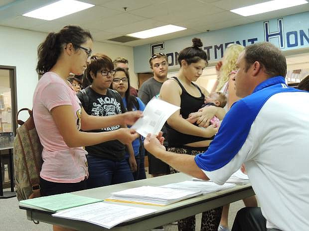 Linda Arreola, a sophomore at Carson High School, receives her schedule from Gavin Ward,  school vice principal, Tuesday, as classmates await their turns. Among courses listed for Arreola were algebra, psychology, history and musicianship in strings and wind ensemble. Her instruments are violin and trumpet. The first day of school at Carson High is Monday. Look for the Appeal's Back to School Section in today's edition.