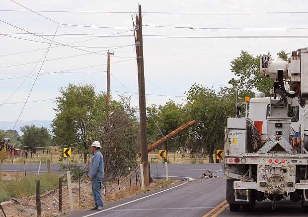 An NV Energy employee surveys the damage done when a big rig's equipment snagged the power liens and brought them down to the ground on Friday at Sheckler Road and Sheckler Cut-off.