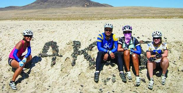 Bike riders draw their line in the dirt near Sand Mountainb as they rode across the Silver State in 2012. From left are  Alice Jiang, Tony Tsai, Sandi Htut and Stephanie Ausfresser after they spelled out 4K with the rocks.