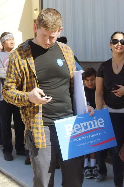 Cooper McCullum, a Bernie Sanders supporter, waits in line.