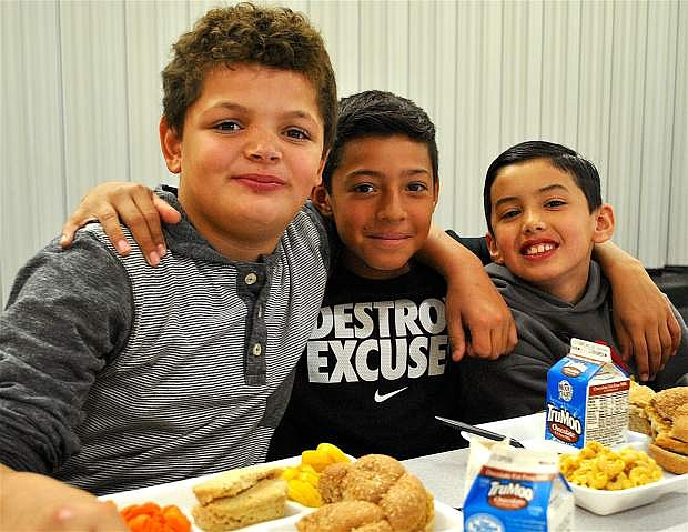 "From left, fourth-graders Isaiah White, Alejandro Chavira and Kekoa Ninoa enjoy eating lunch together in the Numa Elementary cafeteria. ""It's the best food ever!"" White said."