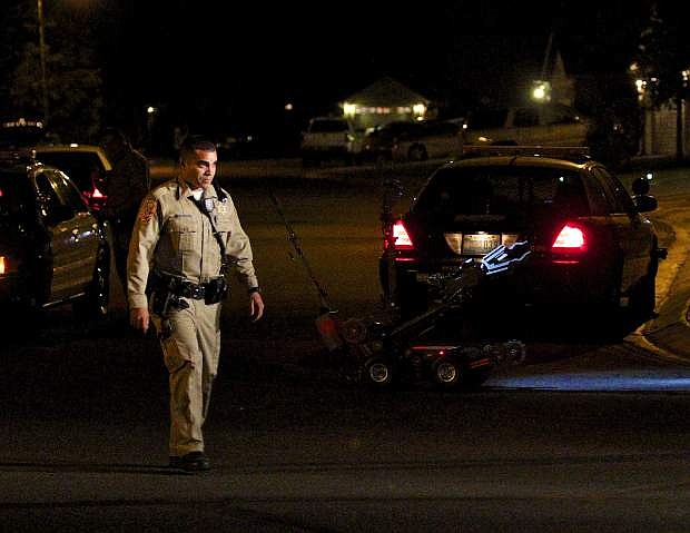A DCSO officer walks back with the robot that was sent in to the house on Edlesborough Circle during a standoff in Gardnerville Tuesday night.