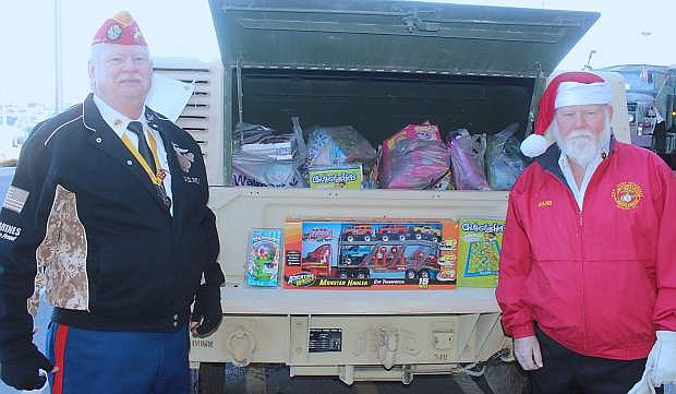 Harry Hines, left, and DD Hansberry show off the toys stored in the back of a Humvee on Saturday at the Toys for Tots collection at Walmart.
