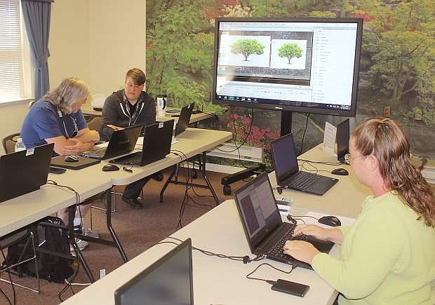 Instructor Lee  Stokes works with students Grey Bynum and Sara Dowling, right, in one of the summer's technology classes offered in a partnership with the Churchill County Library, Western Nevada College and the Churchill Economic Development Authority.