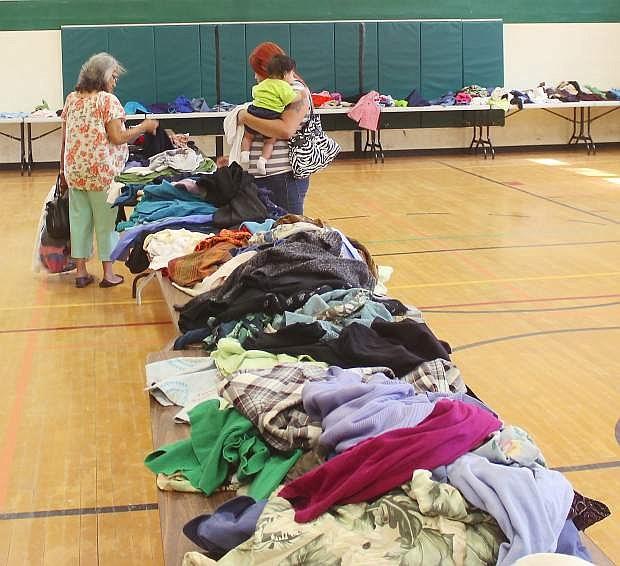 Two women sort through clothes at a previous Fallon Community Days.