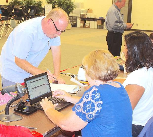 Nate Fiske votes early Tuesday morning as Peggy Ibbeson, left, and Wilma Mansfield use a new computer software program for checking in voters.