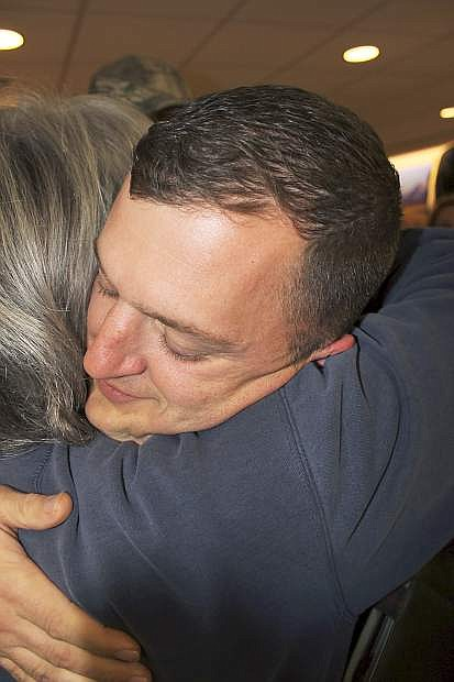 A family friend gives Staff Sgt. Nicholas Scobert a hug after he arrived in Reno.