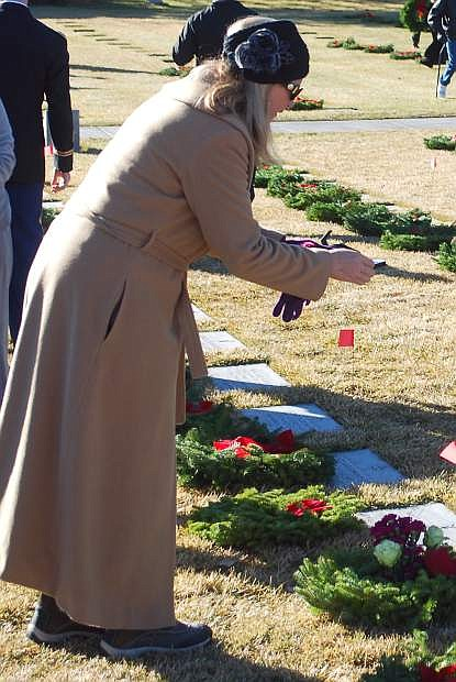 Kelly Beadle of Fallon takes a photo after placing a wreath on her mother's grave at the Northern Nevada Veterans Memorial Cemetery at Fernley on Saturday.