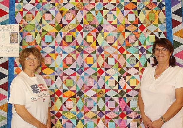 Vicky Eckert, left, and Rory Litch display a quilt that will be raffled on Monday during the final day of the Fallon Cantaloupe Festival and Country Fair. This is the 13th year for raffling a community quilt by the Hearts of Gold quilters. The quilt, Painted Desert, is the work of Kathy Valladon.
