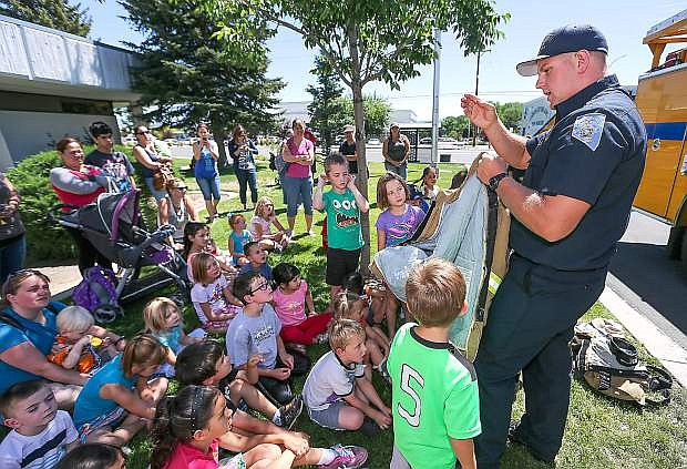 """Carson City Firefighter/Paramedic Matt Cooper talks to a group of children during Storytime at the Carson City Library in Carson City, Nev. on Thursday, June 18, 2015. The event was part of the Summer Reading Program """"Every Hero Has A Story"""" series. For more information about upcoming events, go to www.carsoncitylibrary.org."""