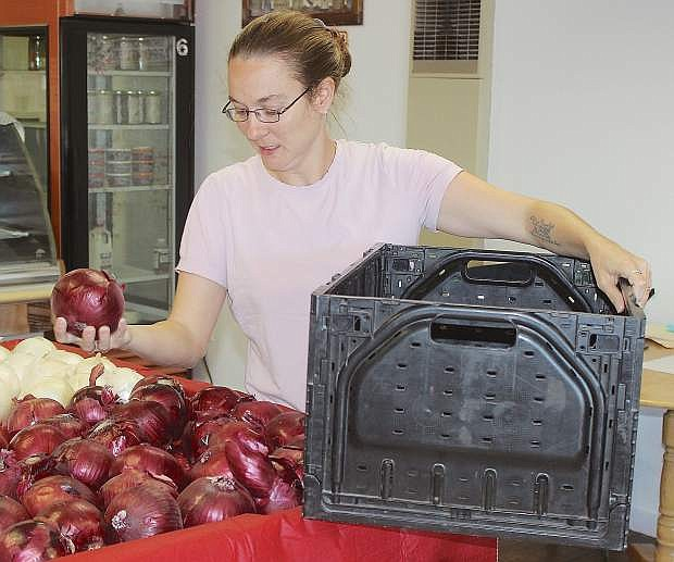 Frances Bourque, store manager of the Fallon Food Hub, begins to place onions from Peri and Sons in a food basket.