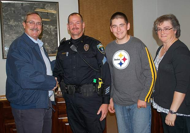 Mayor Ken Tedford Jr., left, congratulates newlypromoted Sgt. John Frandsen of the Fallon Police Dept. Also with the mayor are Frandsen's son, John Michael, and his wife, Kyra.