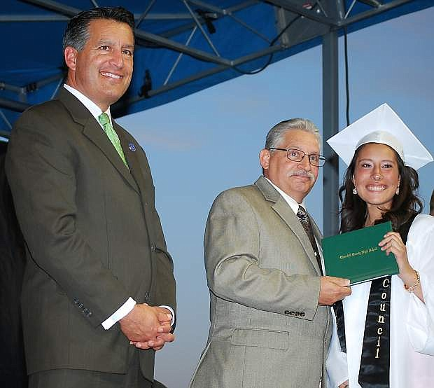Trustee Steve Nunn, center, presents Liz Archuleta with a her diploma Friday during Churchill County High School graduation as Gov. Brian Sandoval looks on.Student speakers praised Archuleta for her spirit and etermination to recover from a stroke.