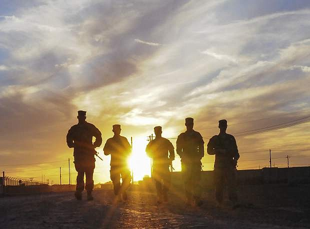 A group of soldiers walk along the road at sunset in Taji,