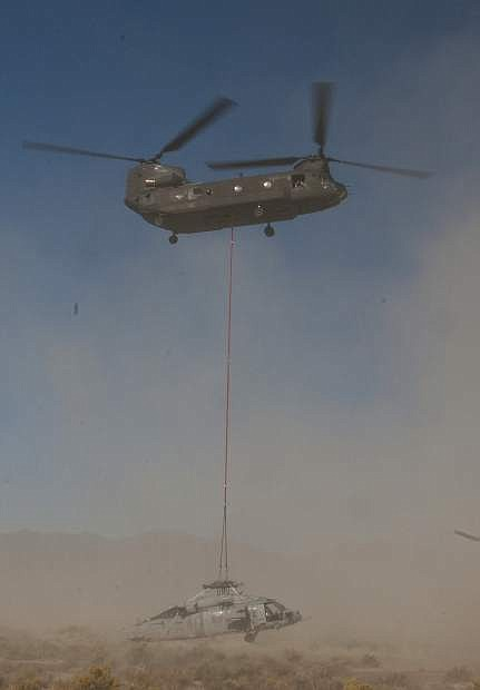 A Nevada Guard 1/189th Aviation Chinook helicopter lifts a Navy Knight Hawk off the Dixie Valley floor on Thursday. The Navy helicopter crashed during a routine training mission Sept. 2.