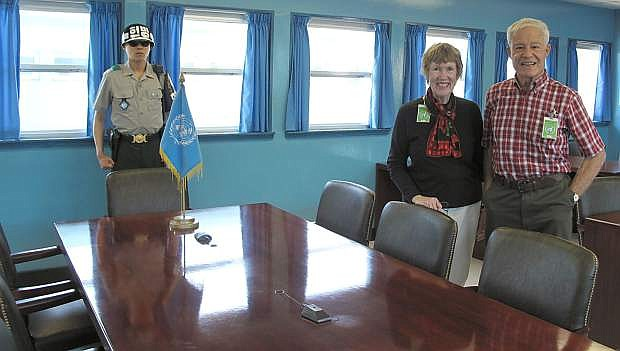 Ludie and David Henley are photographed on the North Korean side of the United Nations conference table, where truce talks have continuously been held since the Korean War ended in 1953. Guarding the South Korean side of the table in a South Korean soldier.