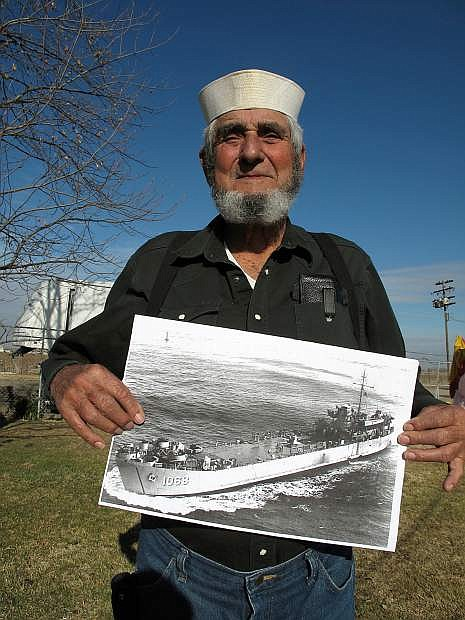 Norman James, 81,  wears his original Navy white hat and holds a photograph of LST-1068 which he served aboard during the Korean War.