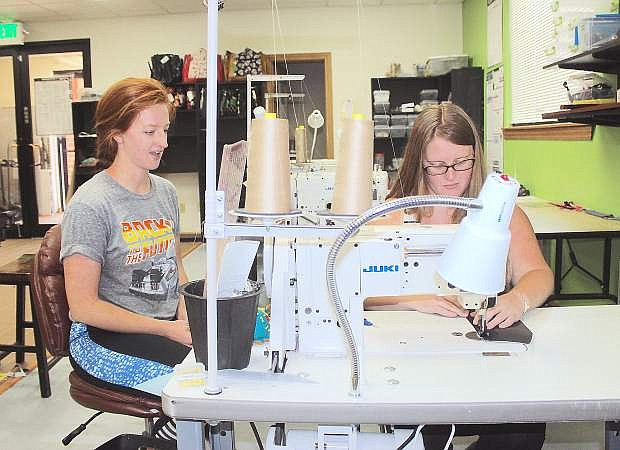 Shayna Jung, left, and Kelsey Coon of Too Cute Totes sew parts of a wallet together.