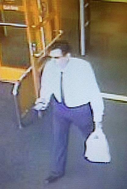 A man walks out of the Target with a bag full of iPads he purchased with a fraudulent credit card.