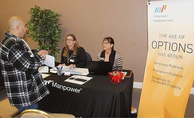 Amber Bixby, left, an Lisa Gonzales of Manpower talk to a job seeker at Friday's job fair.