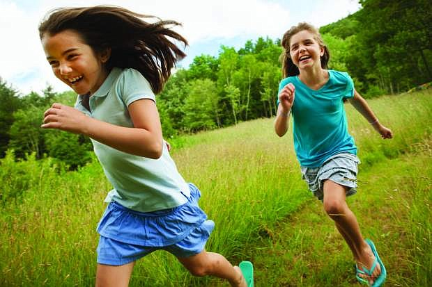 Two children, girls running and playing chase, laugh in the fresh air.