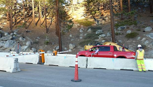 A motorist uses a pass to cross the barricade at the top of Kingsbury Grade on May 1, the first day Kingsbury Grade was closed for construction.
