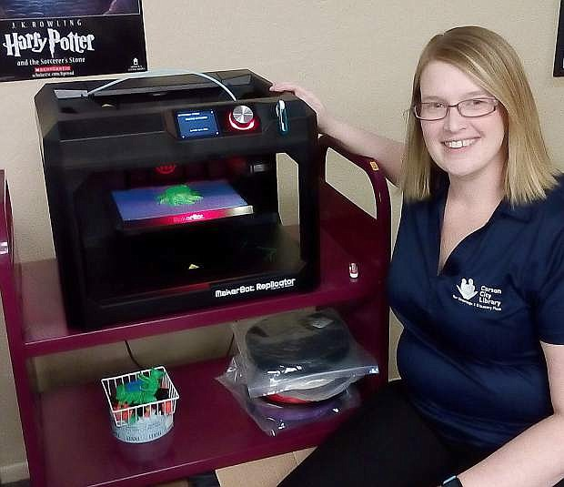 Carson City Librarian Sena Loyd demonstrates one of the new 3-D printing computers now available at the library.