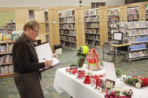Librarian Carol Lloyd looks at some of the centerpieces that have been submitted.