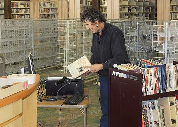 Volunteer Sue Geipel is using a new system to prepare books for checkout.