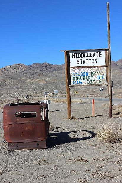 An old, rusted car keeps watch on the Middlegate sign.
