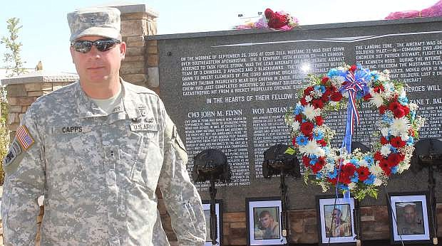 Warrant Officer 2 Roger Capps, the commander of Co. D, 113th Aviation, stands in front of the memorial that honors five soldiers.