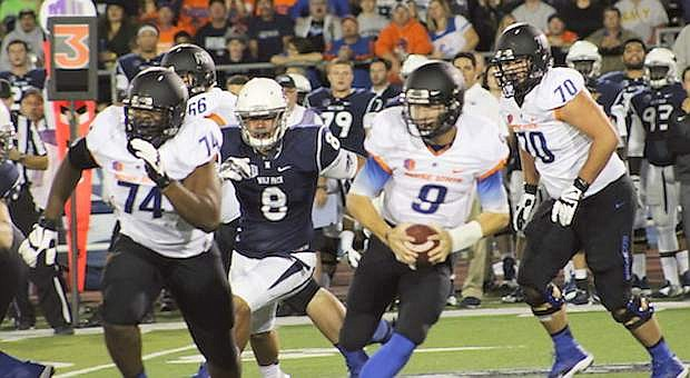 Boise quarterback Grant Hedrick (9) rolls to his left with help from Archie Lewis (74) and Steven Baggett (70). Coming toward Hedrick is the Wolf Pack's Ian Seau (8).
