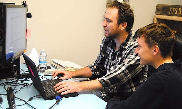 Cody Deegan, right, IT creator of the Oasis Academy website looks over the enrollment process for the high school with his son Kaleb.