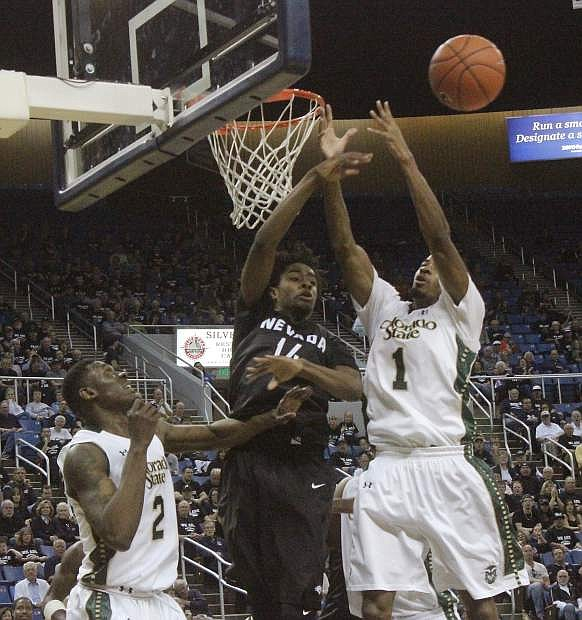 The Wolf Pack's Lindsey Drew (14) rejects CSU's Antwan Scott's shot, while his Rams' teammate Emmanuel Omogbo watches.