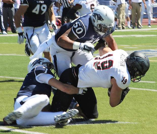 Wolf Pack linebacker Jonathan McNeal (50) wraps up Southern Utah's Chandler Allphin in the first quarter of Nevada's home opener on Saturday against the Thunderbirds.
