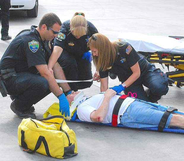 A Fallon police officer and paramedics from Banner Churchill Community Hospital treat Merle Garrison, 69, of St. George, Utah. Neal Stevens, 62, was backing up near a gas pump at the Maverik Gas Center on Monday when he struck Garrison. The Utah man was treated for minor injuries at Banner Churchill and released. No citations were issued.