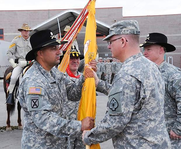 Col. Vernon Scarborough, the commander of the 17th Sustainment Brigade, center, passes the colors of 1st Squadron, 221st Cavalry, to Lt. Col. Michael Peyerl, the incoming commander of the 1-221st, left, on Sunday in North las Vegas. The passing of the colors is a tradition that symbolizes Scarborough entrusting Peyerl with the command previously held by Lt. Col. Michael Glynn, right.
