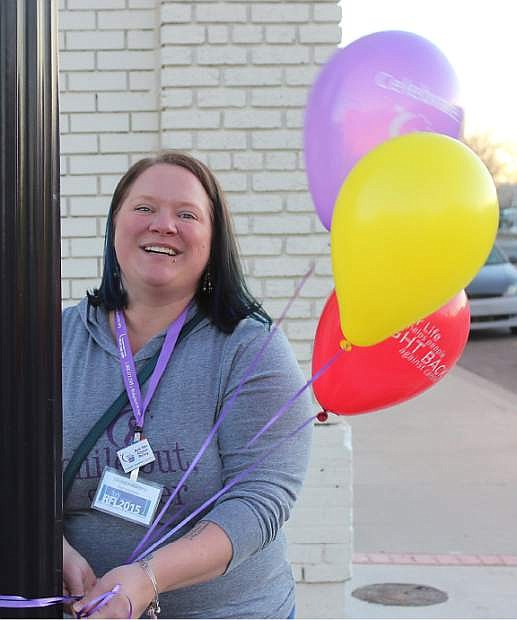 Melissa Williams ties Relay for Life balloons around a post in front of the Elks Lodge.