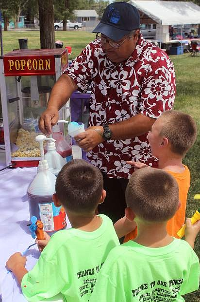 Manny Rosse adds flavorings to some snow cones.