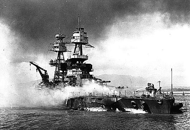 USS Nevada (BB-36) beached and burning after being hit forward by Japanese bombs and torpedoes. Her pilothouse area is discolored by fires in that vicinity. The harbor tug Hoga (YT-146) is alongside Nevada's port bow, helping to fight fires on the battleship's forecastle. Note channel marker bouy against Nevada's starboard side.