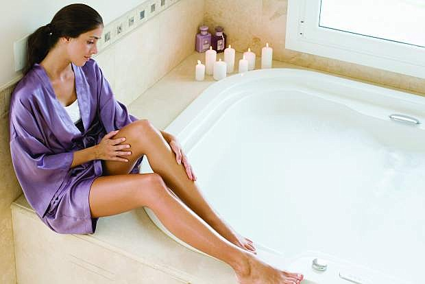 A woman who is taking care of her skin sits near the bath.